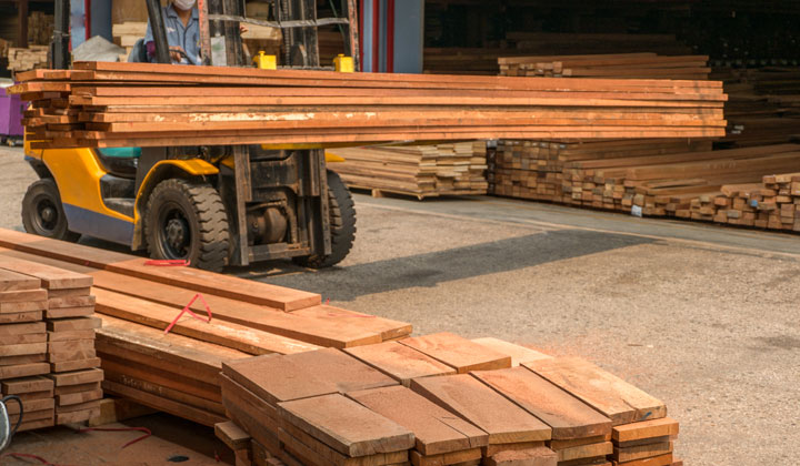 forklift moving wood boards at lumber mill